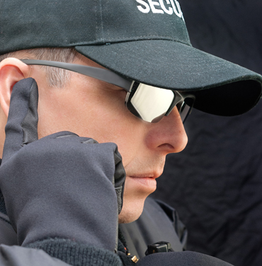 Close-up of a close protection officer listening to his earpiece.